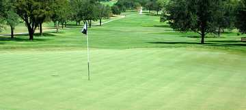 A view of a green with narrow road on the left at San Antonio Country Club